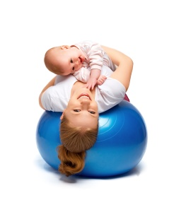 mother and baby doing gymnastic exercises on the ball