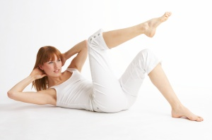 young woman making sit- ups - junge Frau macht sit- ups
